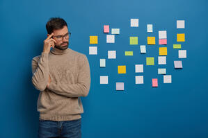 people-work-thoughts-concept-contemplative-bearded-guy-keeps-finger-on-temple-looks-pensively-aside-puts-colorful-sticky-notes-on-wall