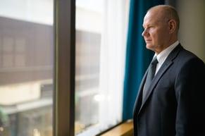 senior-businessman-thinking-while-looking-through-the-window