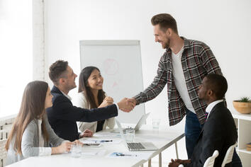 smiling-businessman-welcoming-new-partner-at-group-meeting-with-handshake