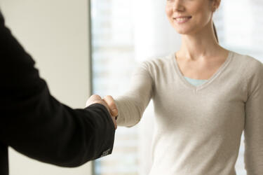 smiling-businesswoman-shaking-businessman-hand-in-office