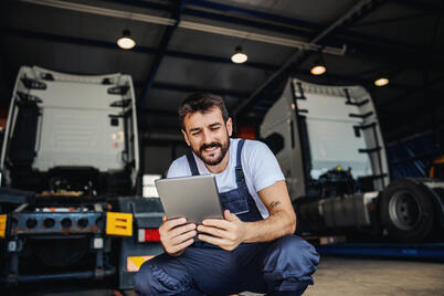 smiling-tattooed-bearded-blue-collar-worker-in-overalls-using-tablet-to-check-on-delivery-while-crouching-in-garage-of-import-and-export-firm
