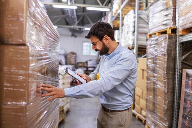 supervisor-in-warehouse-standing-next-to-boxes-and-using-tablet-to-check-on-goods